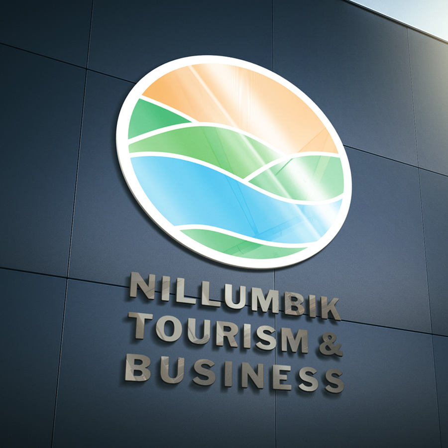 Mockup of the logo design for Nillumbik Tourism & Business. Features a glossy 3D logo on the side of a glass building.