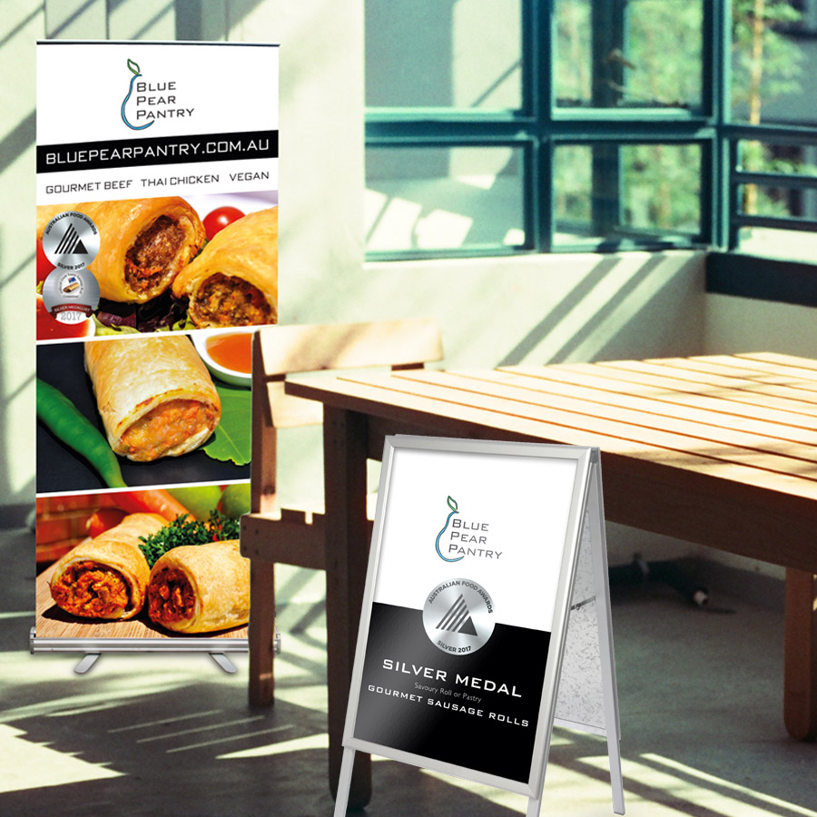 Pull-up banner and A-Frame design mockup for Blue Pear Pantry, maker of gourmet sausage rolls