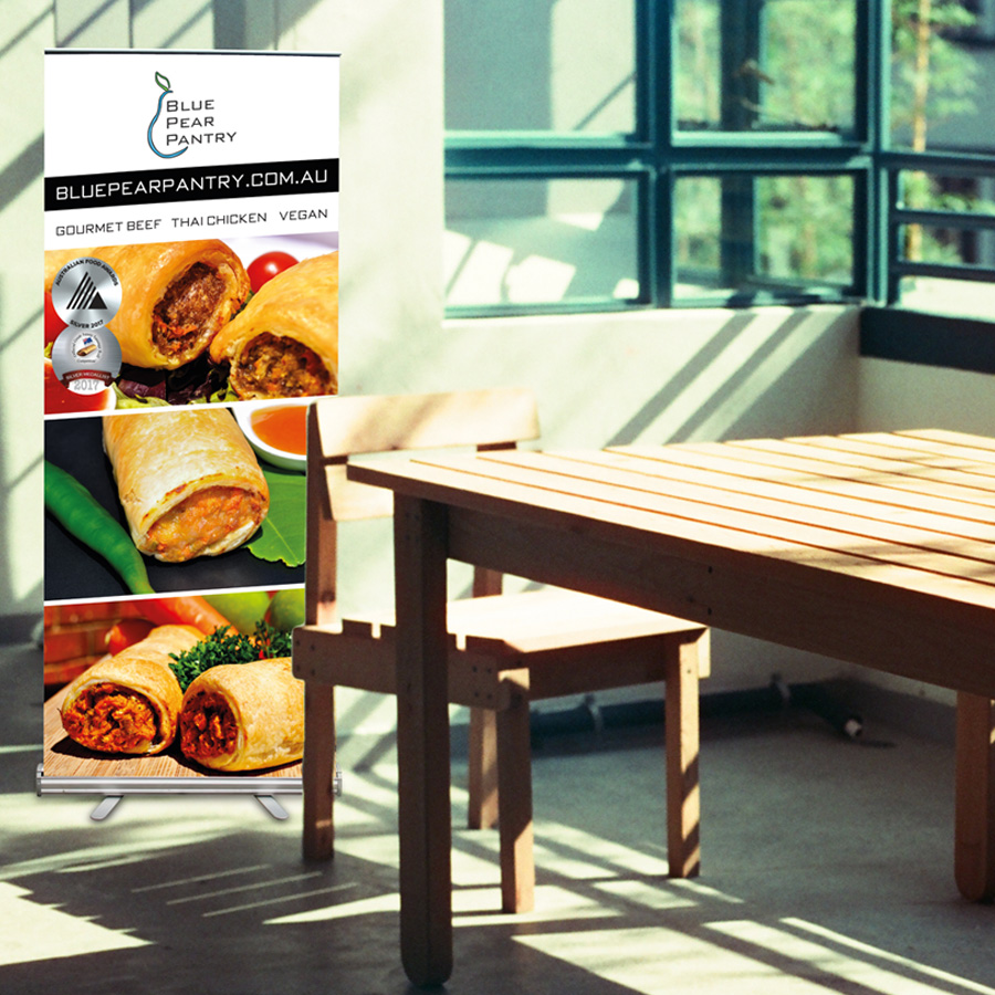 Mockup of a pull-up banner designed for Blue Pear Pantry featuring 3 types of sausage rolls.